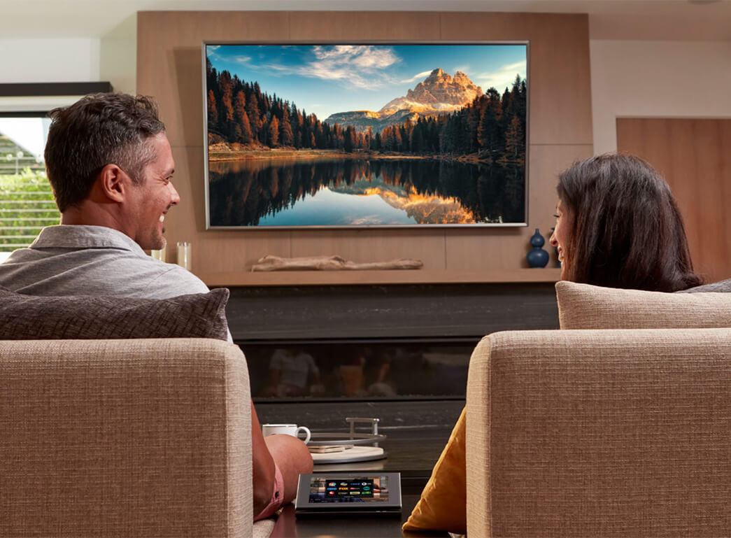 Couple Smiling In From Of Television